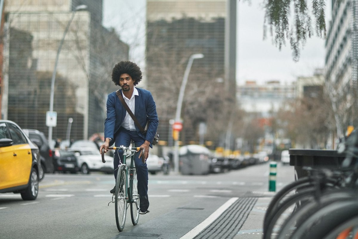 A person wearing business clothes and riding a bike on a city street.