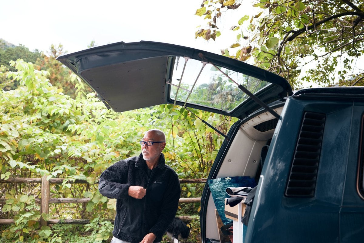 A person standing next to the open trunk door of a car and zipping up their jacket.