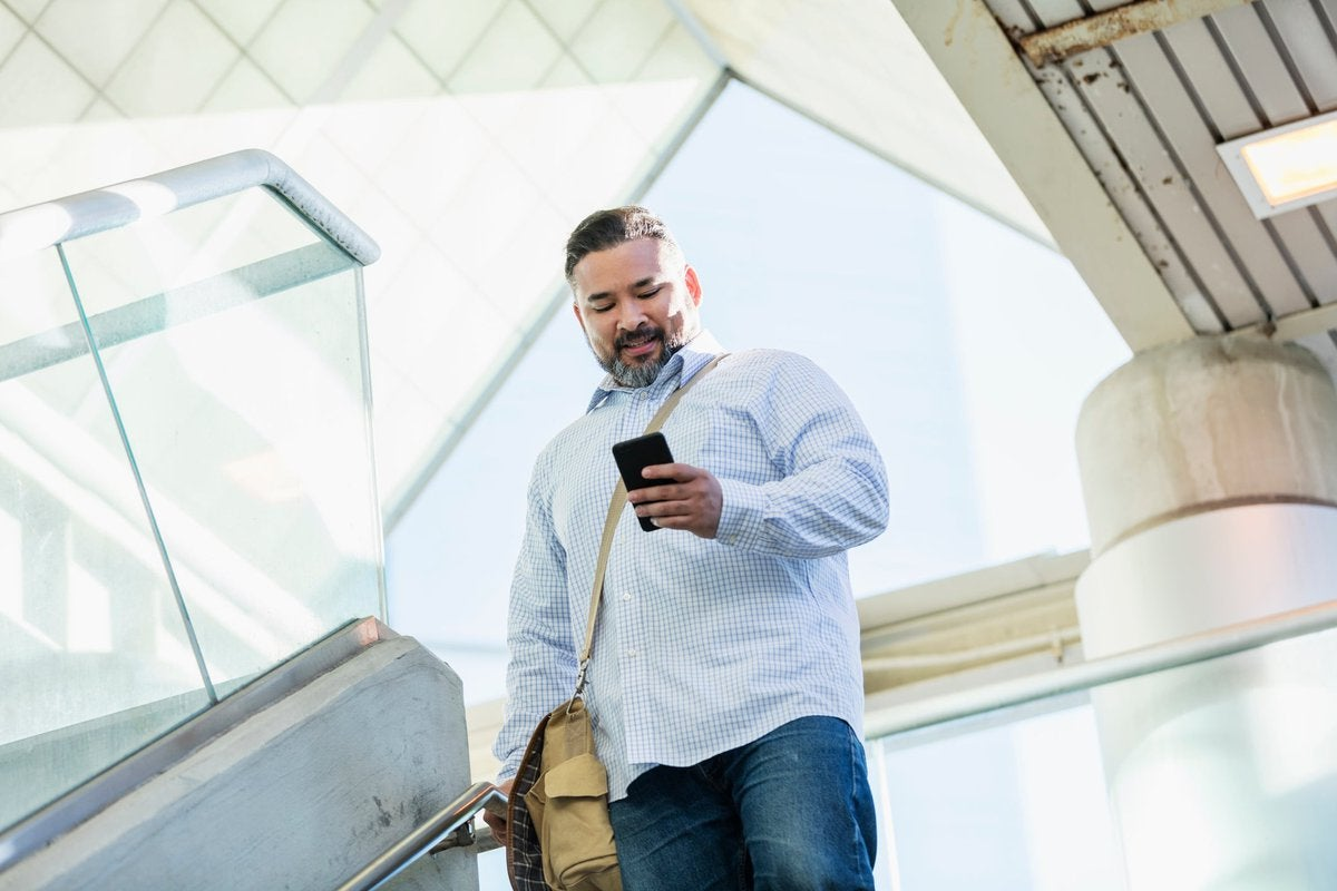 A person walking down stairs while smiling and looking at their phone.