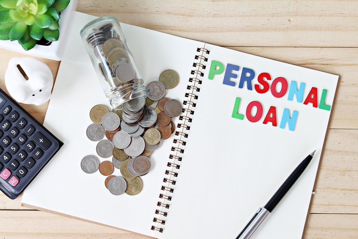 Open notebook with a jar of spilled coins and colorful letters that spell out PERSONAL LOAN