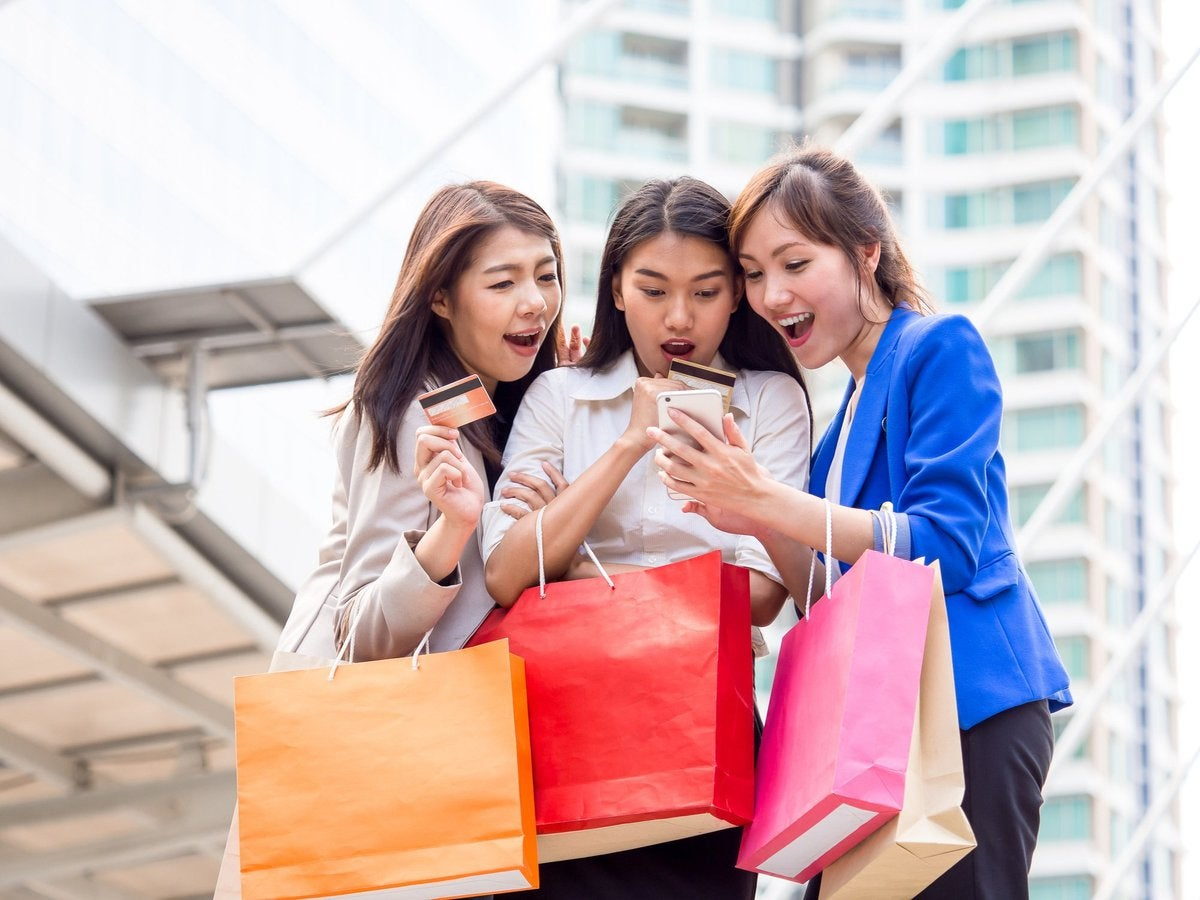 three girls holding shopping bags and credit cards taking a selfie