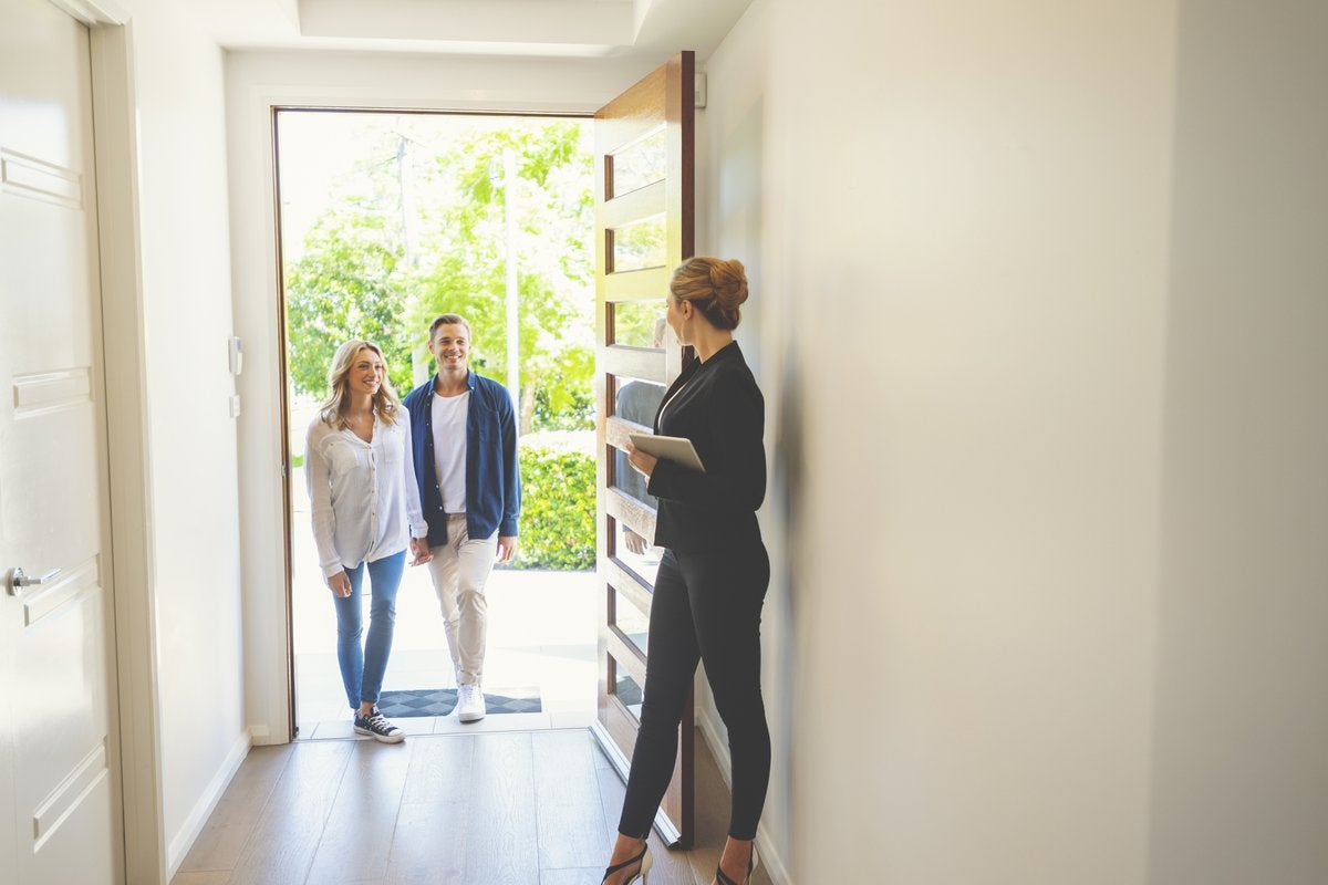 A realtor opening the door of a new home for a young couple.