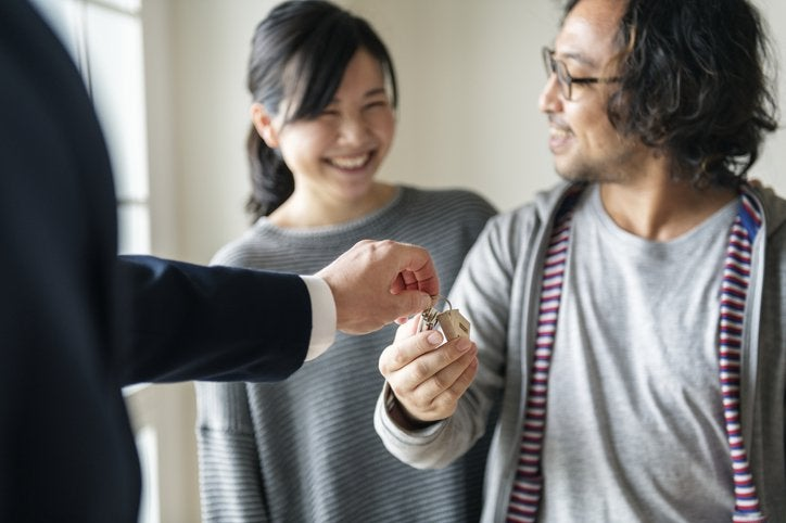 A realtor handing a set of house keys to a smiling man and woman.