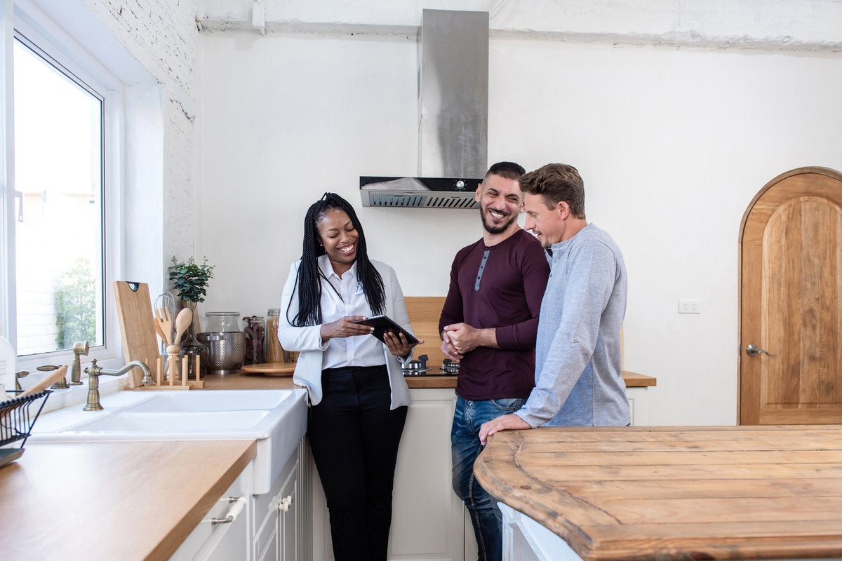 A realtor showing a smiling couple a new home.