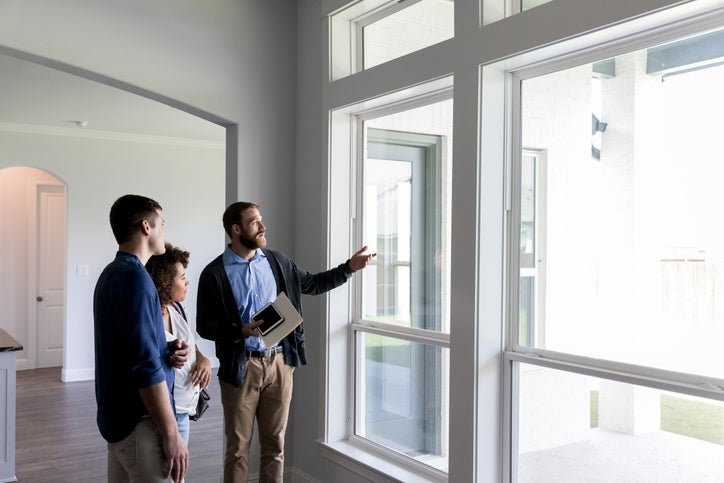 A realtor walking his clients through an empty house and pointing out the window.