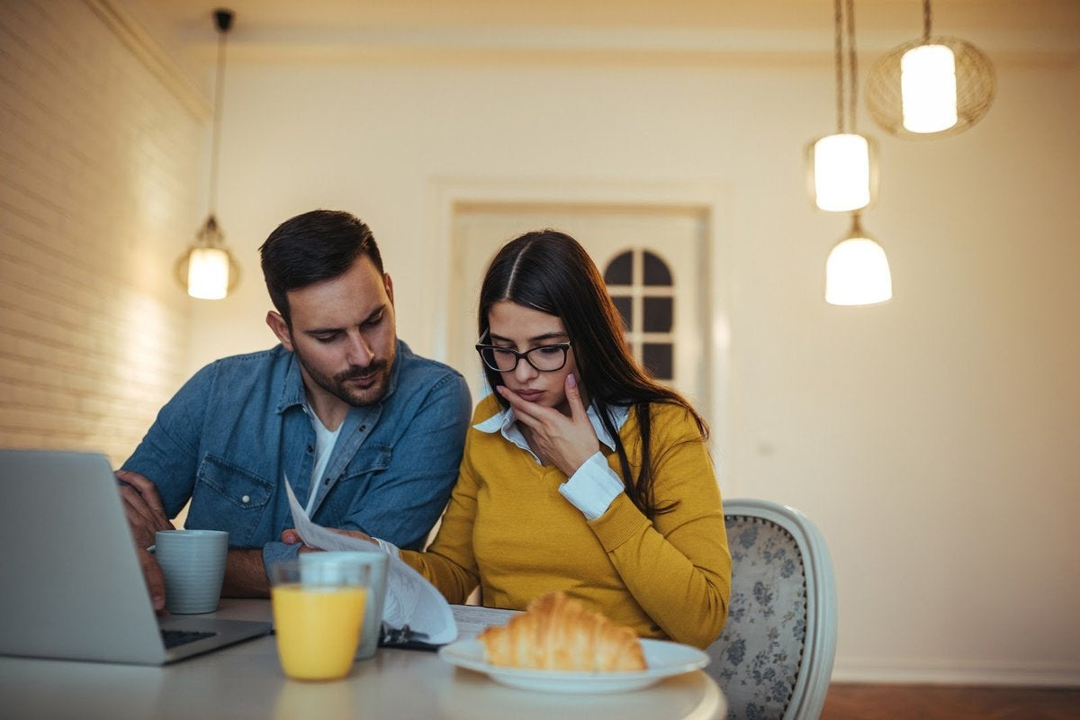 Couple eating breakfast looking at laptop and papers concerned.
