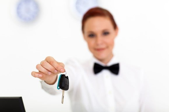 car rental company employee handing over car key to client