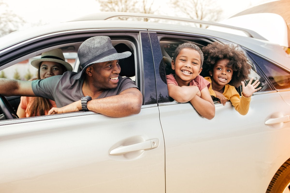 Family of four smiling and waving out of a car.