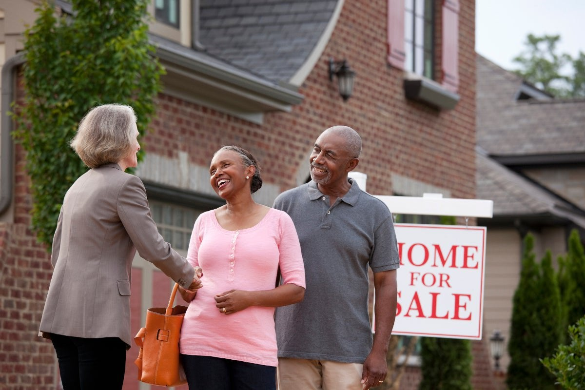 A couple shakes a realtor's hand in front of a home for sale.