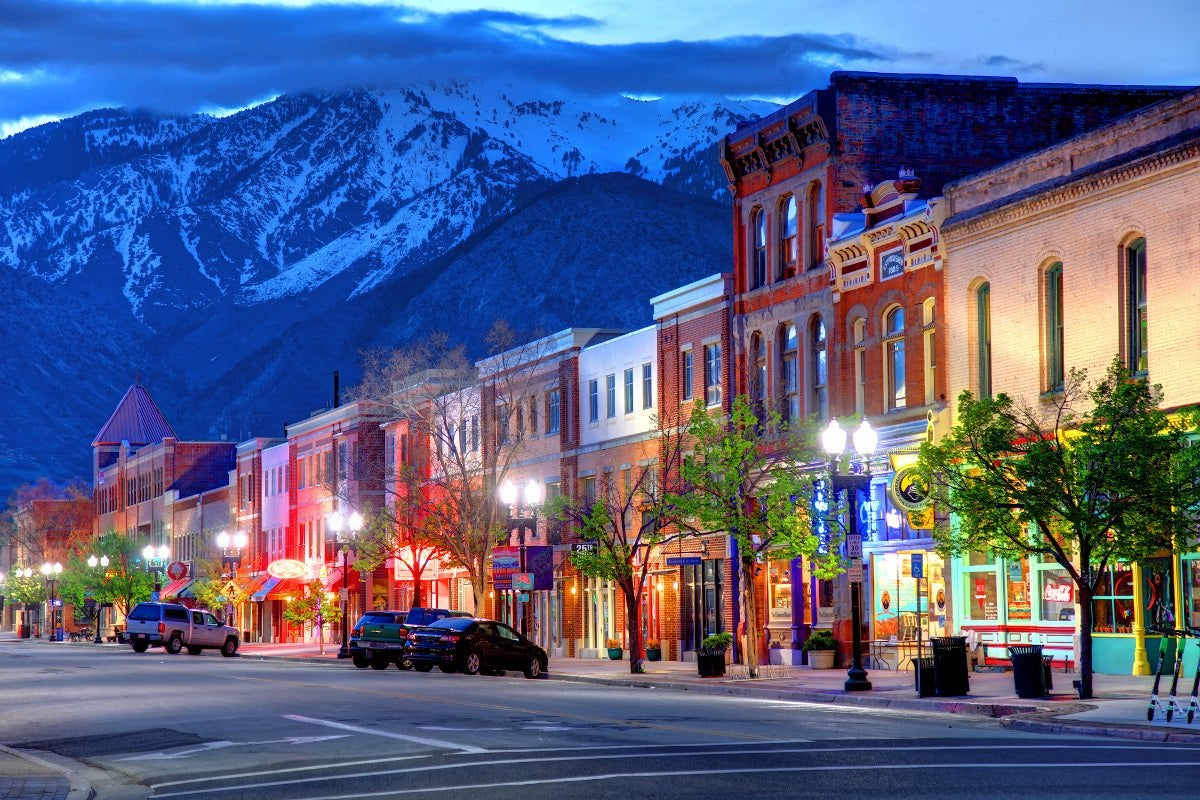 A shopping street in Ogden, Utah, at dusk, in front of a snowcapped mountain.