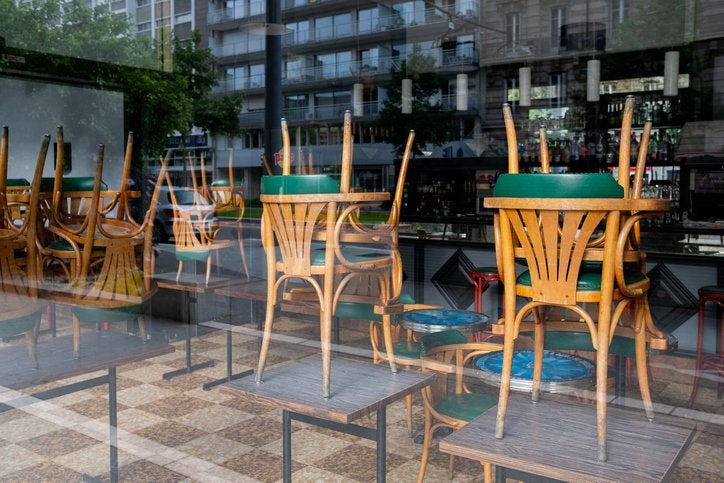 Chairs stacked on top of tables in an empty restaurant window.