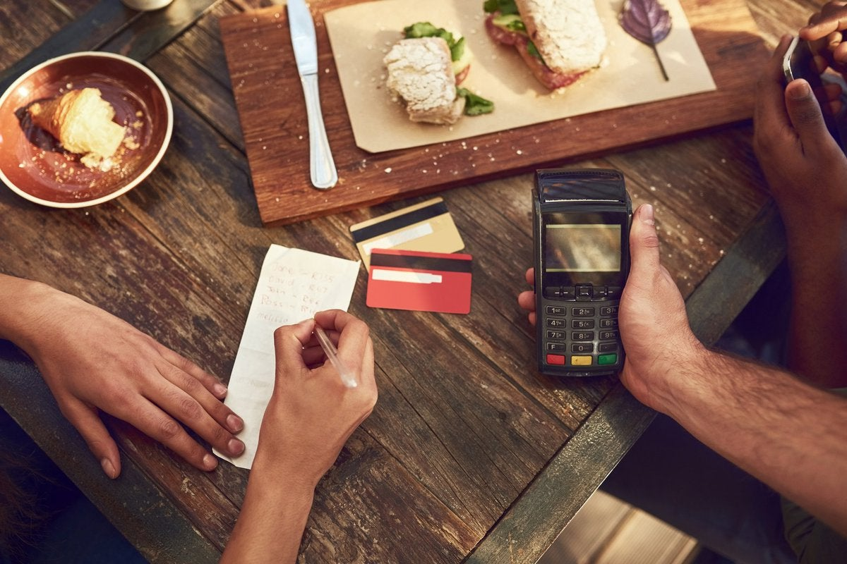 A woman signing the receipt for her credit card payment while the waiter holds the card reader after finishing lunch at a restaurant.