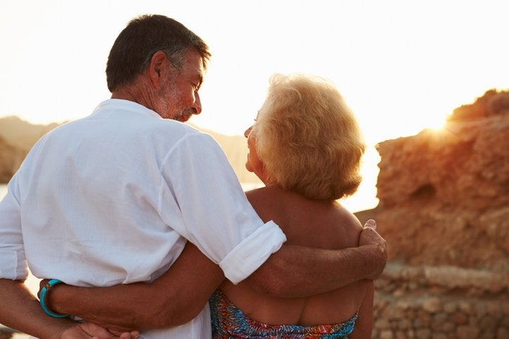 An older couple standing on the beach and looking at the sunset with their arms around each other.