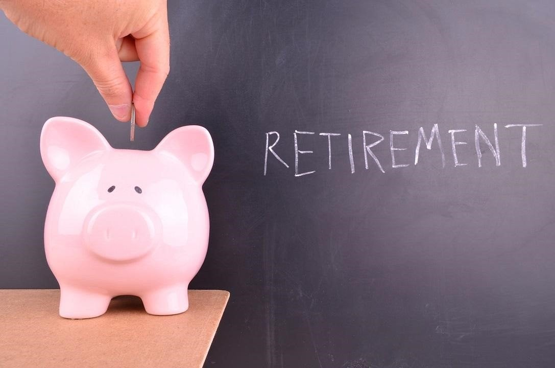 A hand putting coins into a piggy bank with the word Retirement behind it on a chalk board.
