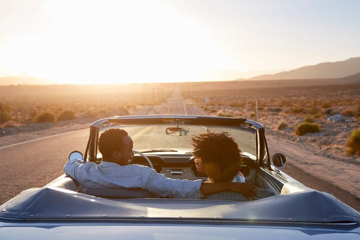 A couple on the road in a convertible.