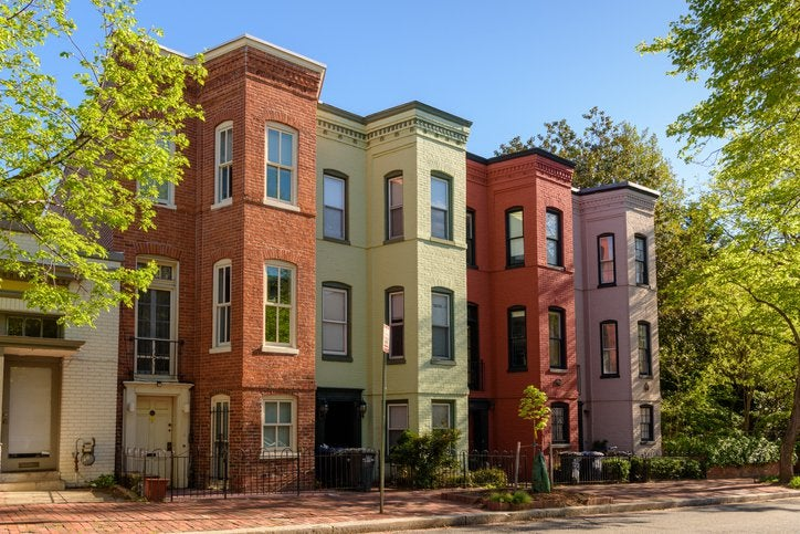 A row of colorful multistory houses in a city on a sunny street with green trees.