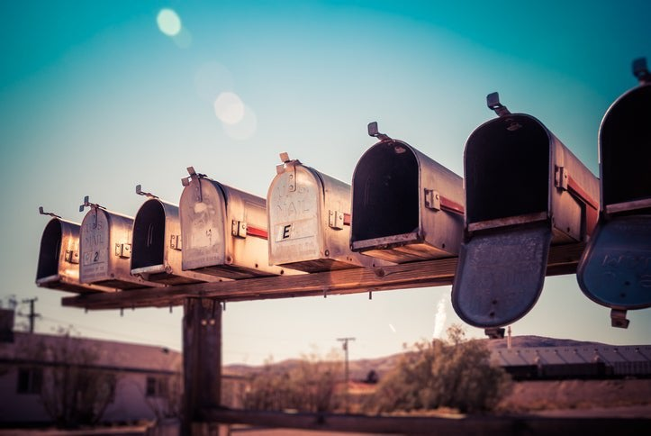 A row of empty mailboxes on a rural road.