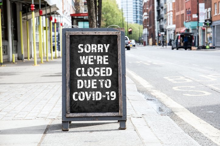 A sandwich board on a sidewalk that reads Sorry We're Closed Due to COVID-19.