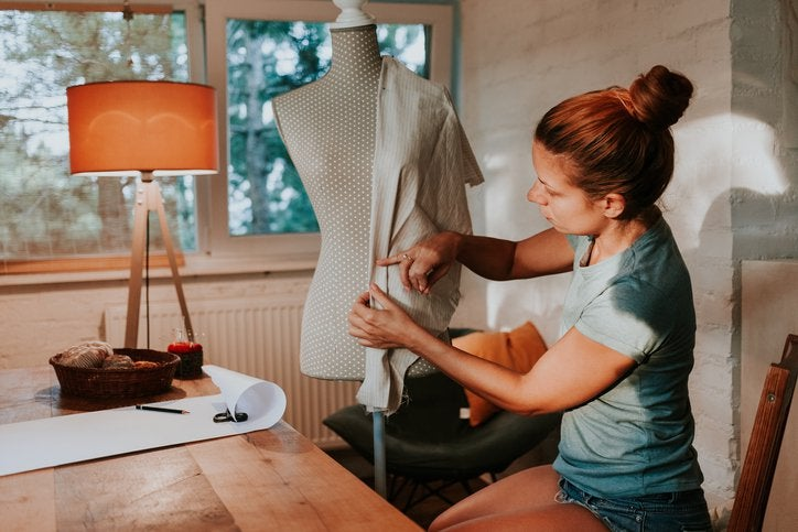 A seamstress holding up a piece of cloth to a body form in her home studio.
