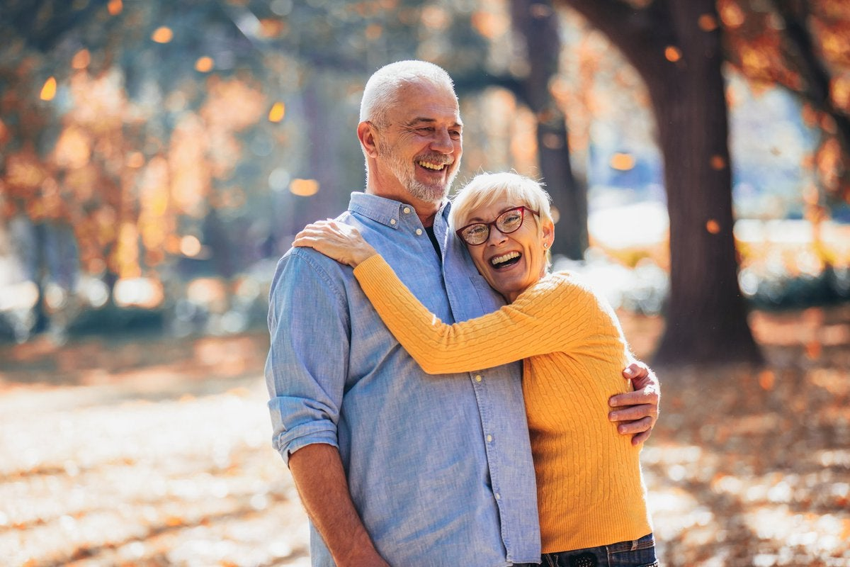 senior man and woman hugging and laughing
