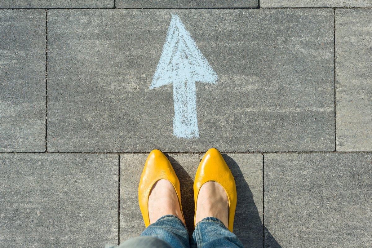 woman's feet standing behind an arrow pointing forward