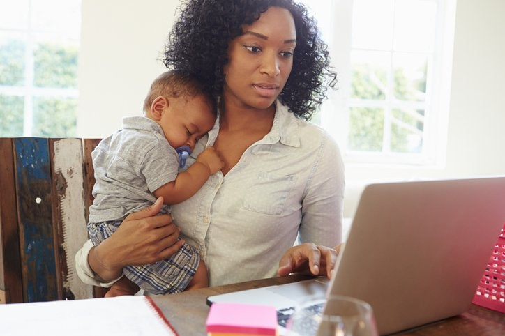 A mother holds an infant while she works on her computer.