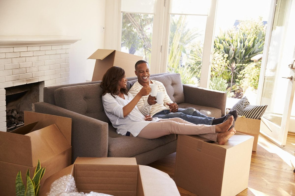 A smiling couple toasting with coffee mugs on a couch surrounded by moving boxes.