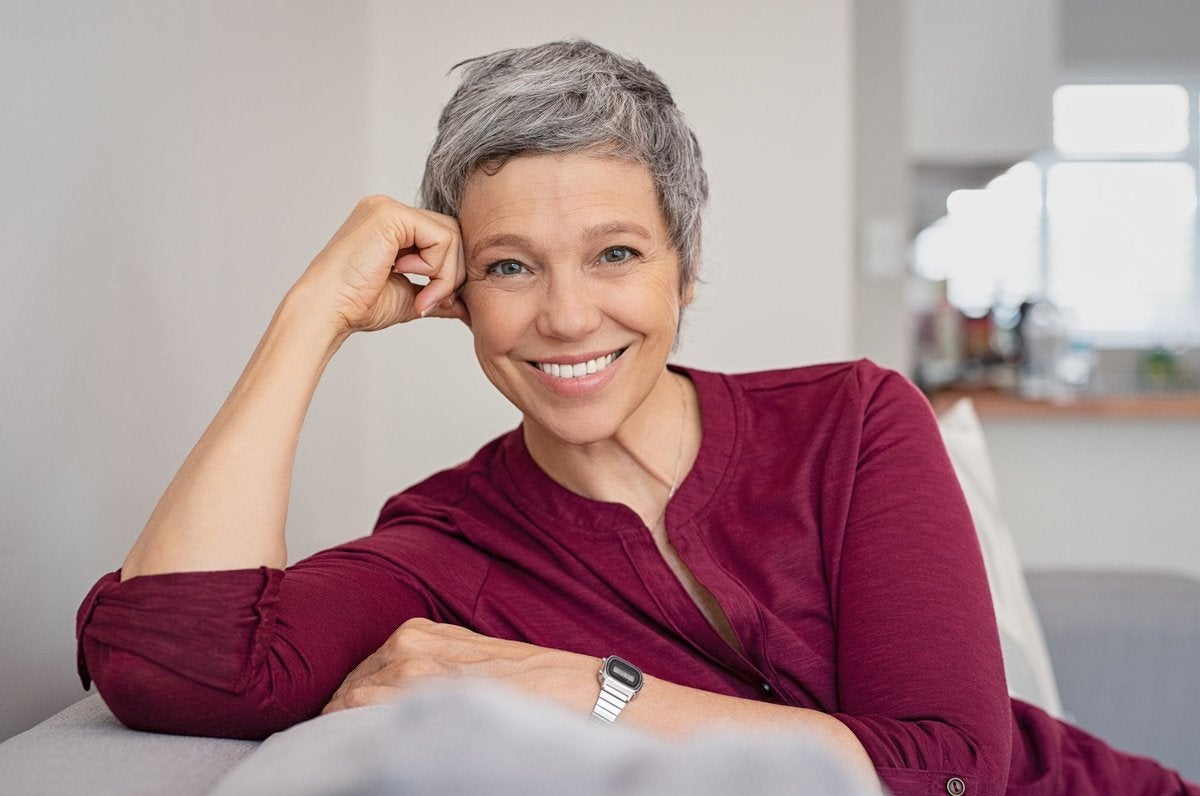 Smiling older woman resting hand against head