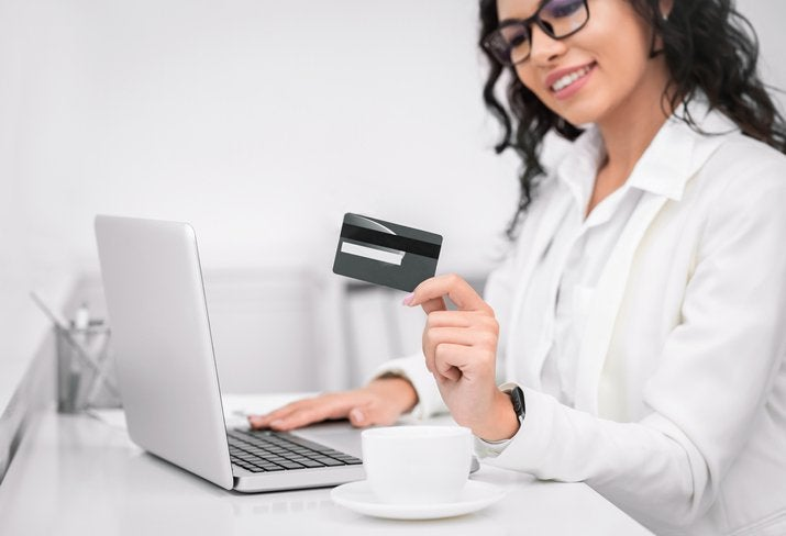 A smiling woman holds a credit card.