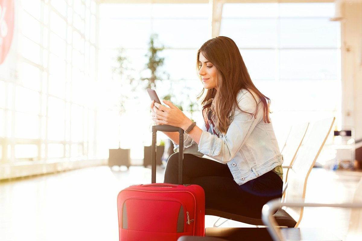 Smiling woman with suitcase typing on phone in airport