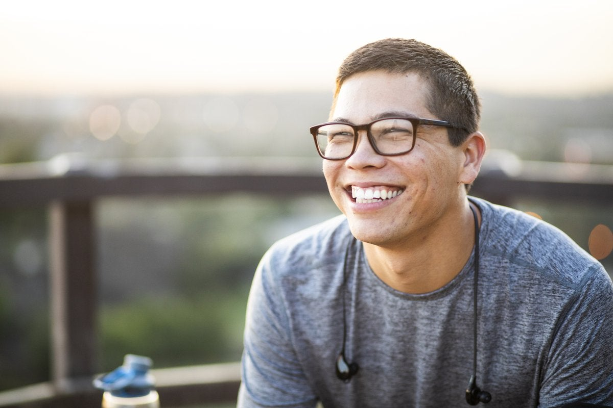 A smiling young man sitting at an outdoor patio.