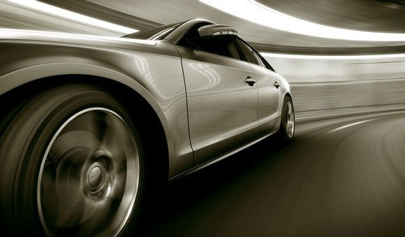 Black-and-white photo of sports car driving through tunnel