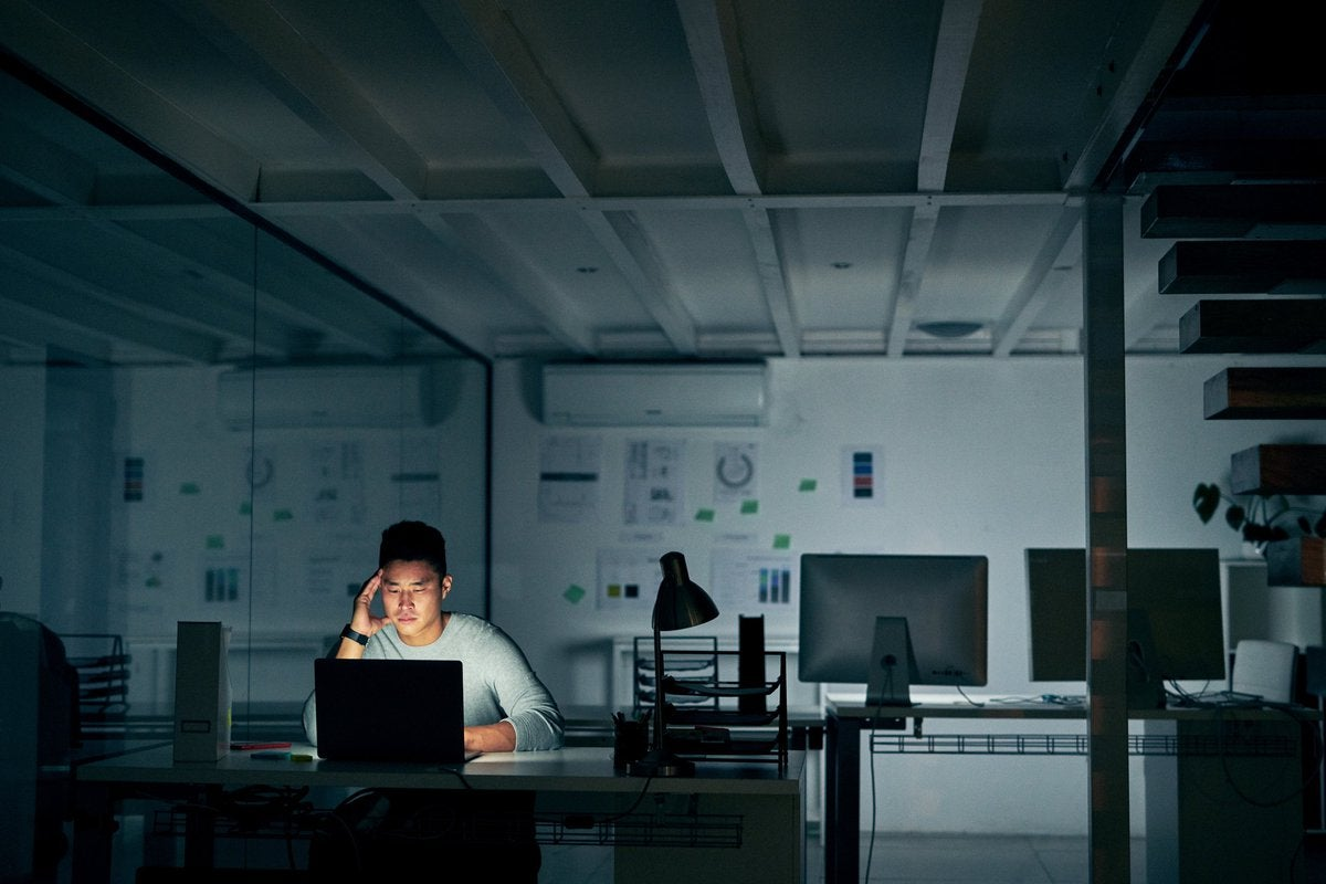 A stressed young man sitting in front of a laptop in a dark office.