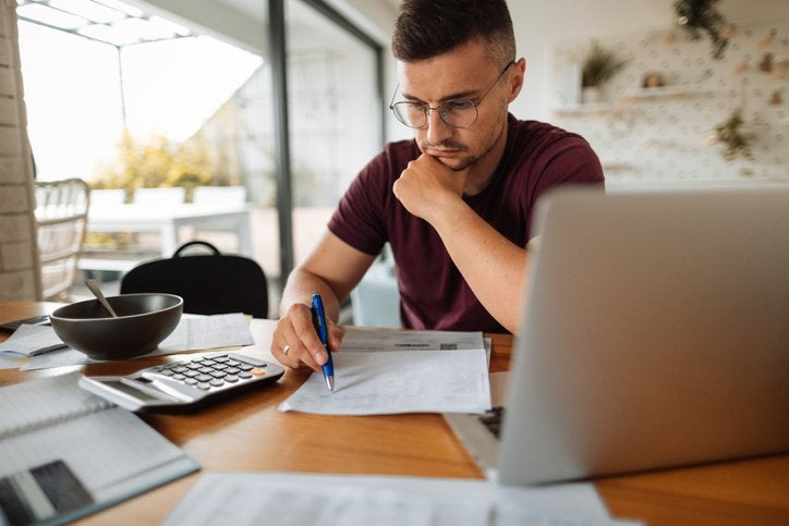 A man looking stressed while going through his bills next to his open laptop.