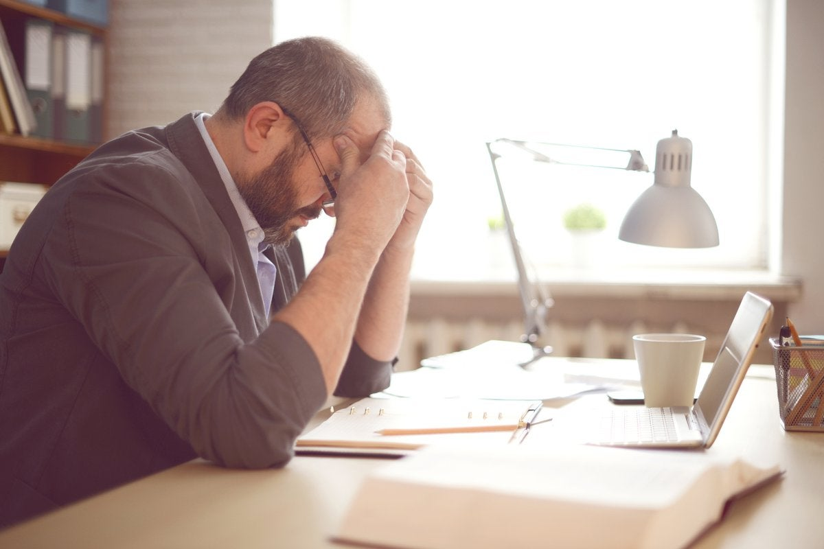 A stressed man working at a desk with his head in his hands.