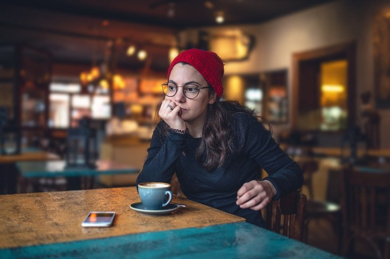 A stressed woman sitting in a cafe with her chin resting in her hand.