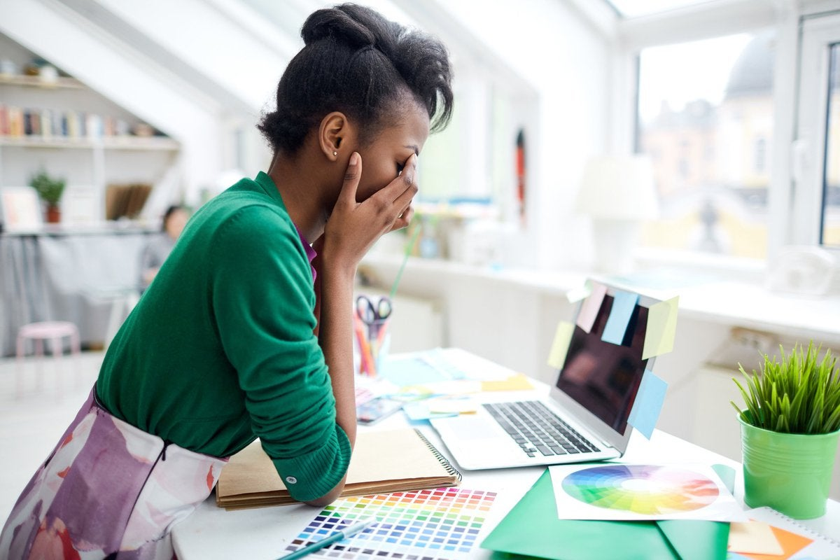 A stressed young woman sitting at her desk in front of a laptop with her face in her hands.