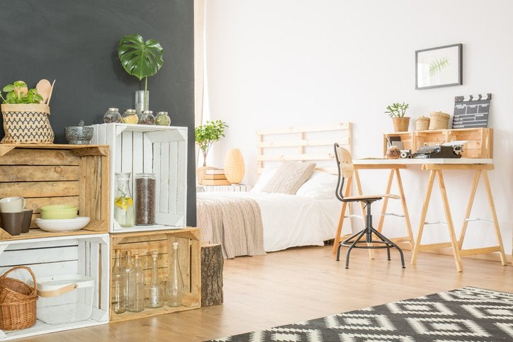 A sunny studio apartment with a desk, low bed, and wooden crates for shelves,