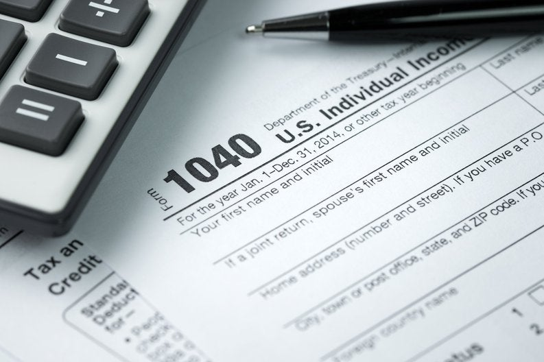 IRS tax form 1040 next to pen and calculator.