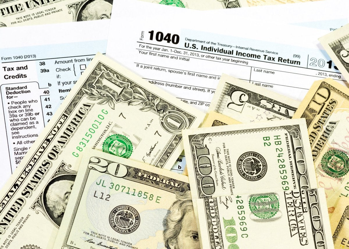 Various dollar bill amounts on top of tax forms.