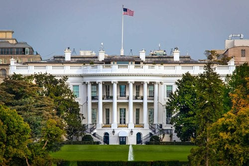 The White House surrounded by trees and a lawn with the American flag flying at the top of the building.