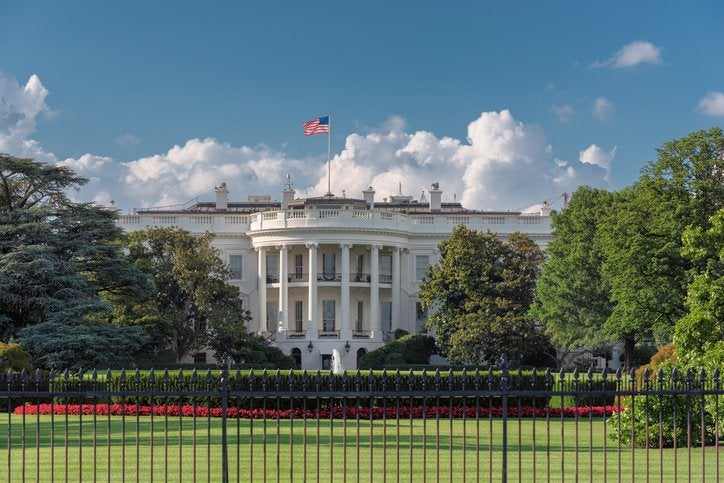 The White House with a blue sky and puffy white clouds behind it.