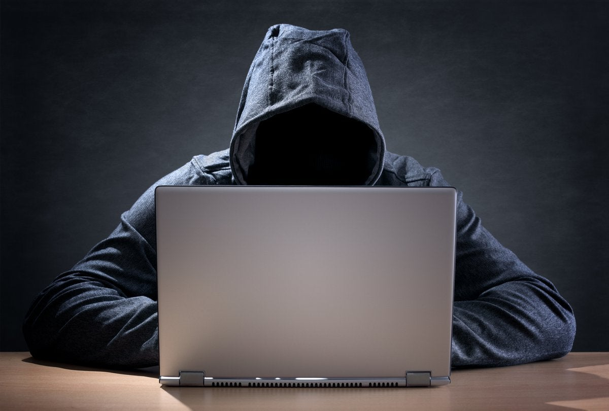 A cyber criminal wearing a hoodie and using a laptop.