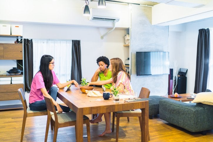 Three female roommates sitting around the dining table in their apartment.