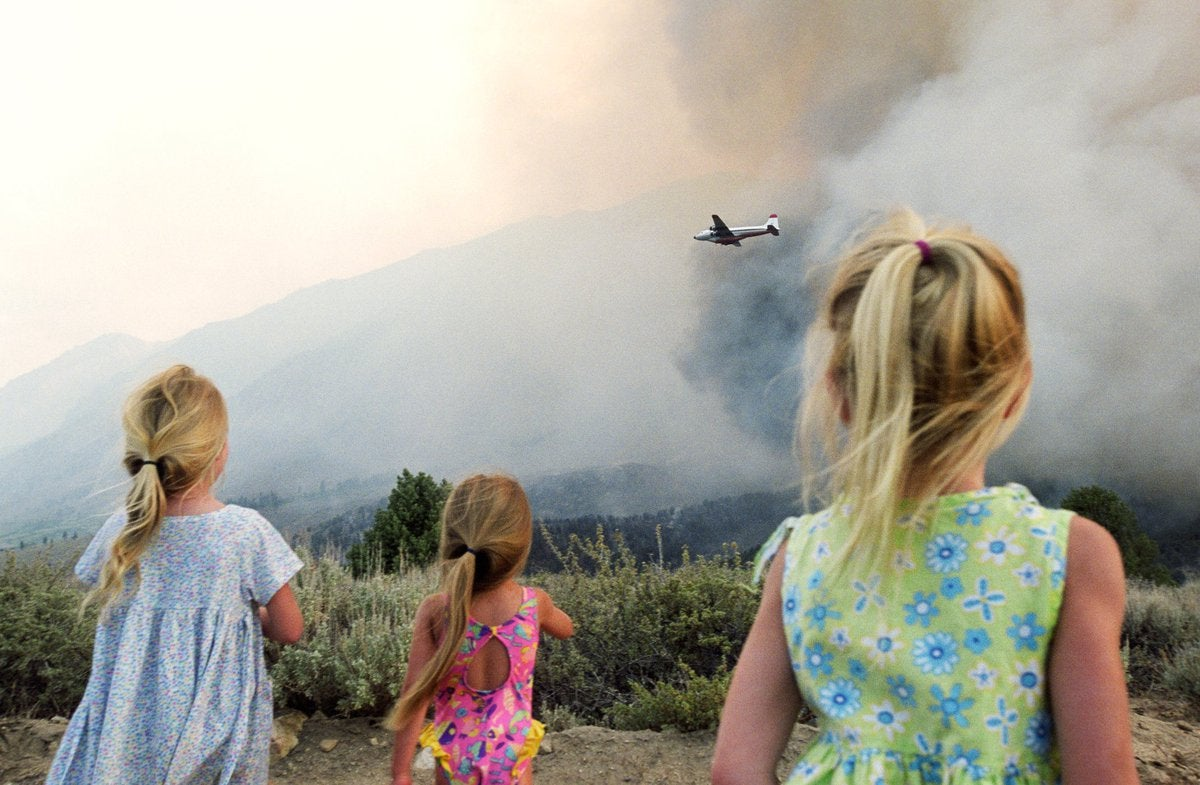 Three young children watching a firefighting plane fly over wildfire smoke.