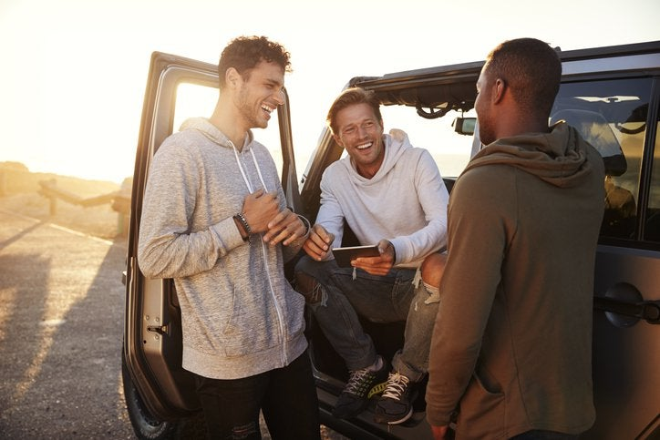 Three smiling men standing around their car and planning their road trip route on a phone.