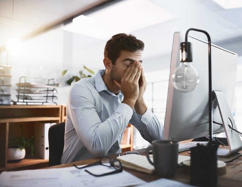 A tired man rubbing his eyes and sitting at his desk at work.