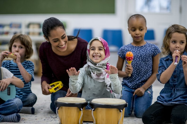 Young children having fun at daycare playing with instruments.