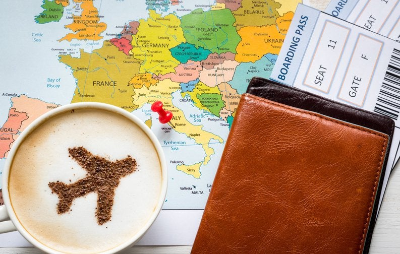Airplane in cup of coffee on top of map with boarding pass