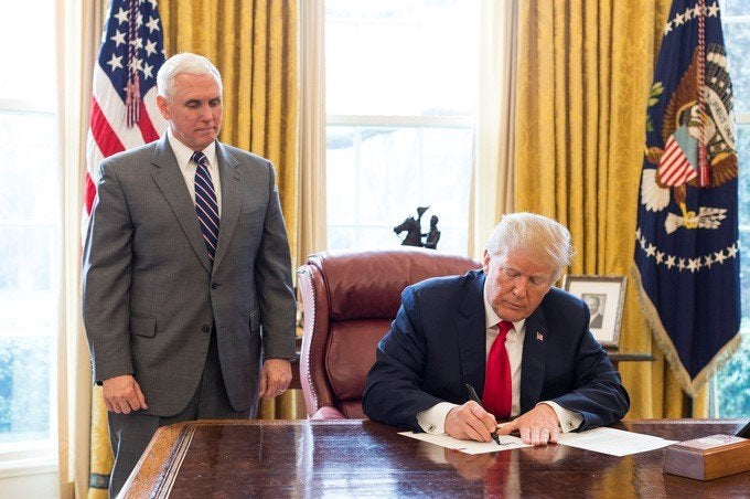 President Trump signing an executive order in the Oval Office.